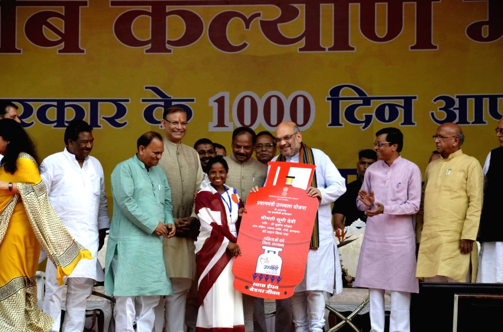 """BJP chief Amit Shah distributes free LPG connection to a tribal during the """"Poor Welfare Fair"""" in Ranchi on Sept 16, 2017. Also seen Jharkhand Chief Minister Raghubar Das and Union ... - Raghubar Das, Amit Shah and Aviation Jayant Sinha"""