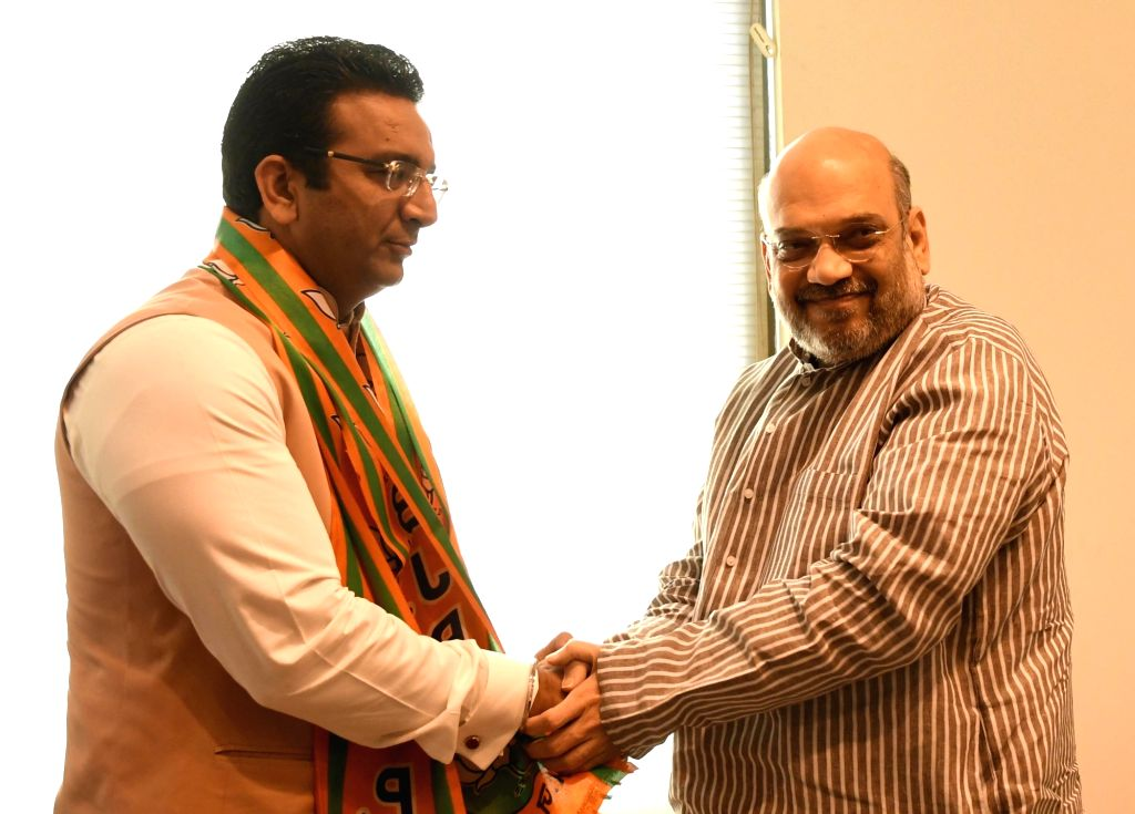 BJP chief Amit Shah greets former Samajwadi Party (SP) leader and spokesperson Gaurav Bhatia, who joined  BJP in New Delhi on April 2. 2017. - Amit Shah