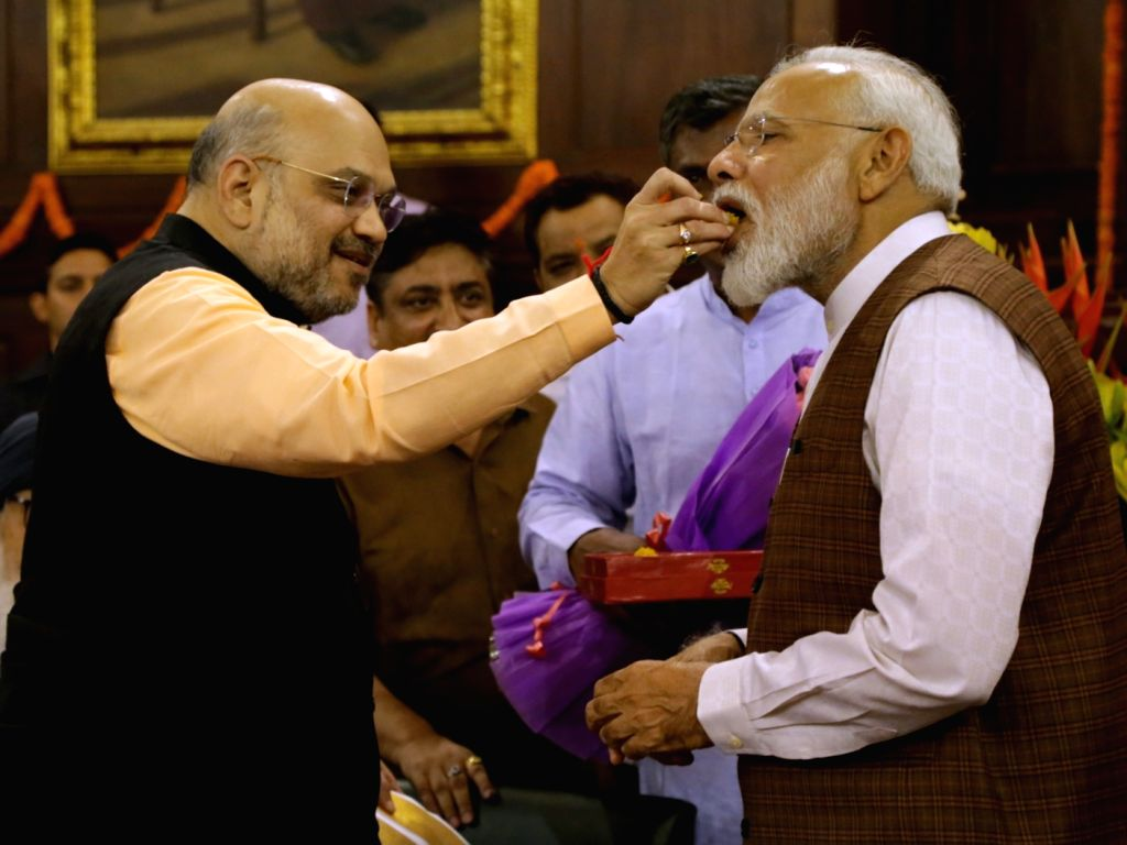BJP chief Amit Shah greets Prime Minister Narendra Modi during NDA Parliamentary Board meeting at the Central Hall of Parliament, in New Delhi on May 25, 2019. - Narendra Modi and Amit Shah