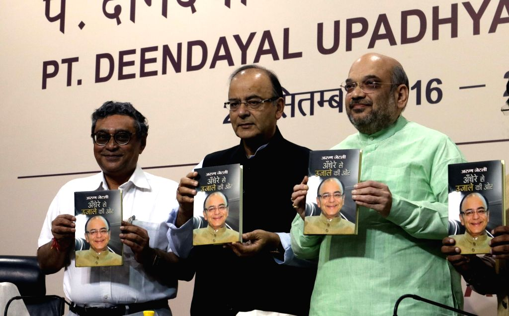 "BJP chief Amit Shah, Union Finance Minister Arun Jaitley and Rajya Sabha MP Swapan Dasgupta unveil a book ""Andhere Se Ujale Ki Aur"" by Arun Jaitley in New Delhi on Oct 20, 2016. - Arun Jaitley and Amit Shah"