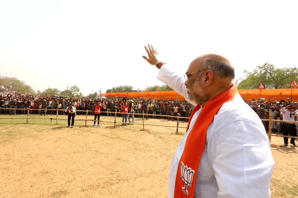 BJP chief Amit Shah waves at supporters during a public rally in Pakur, Jharkhand on May 11, 2019. - Amit Shah