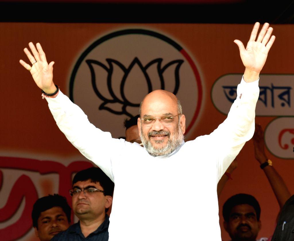 BJP chief Amit Shah waves at supporters during a public rally at Rajarhat in Kolkata on May 13, 2019. - Amit Shah