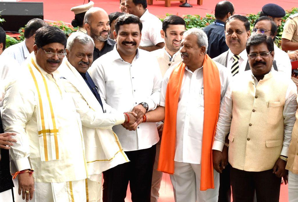 BJP leader and Karnataka Chief Minister B.S. Yediyurappa's son BY Vijayendra greets the newly inducted Karnataka Cabinet Ministers in Bengaluru on Feb 6, 2020. Karnataka Governor Vajubhai ... - B.
