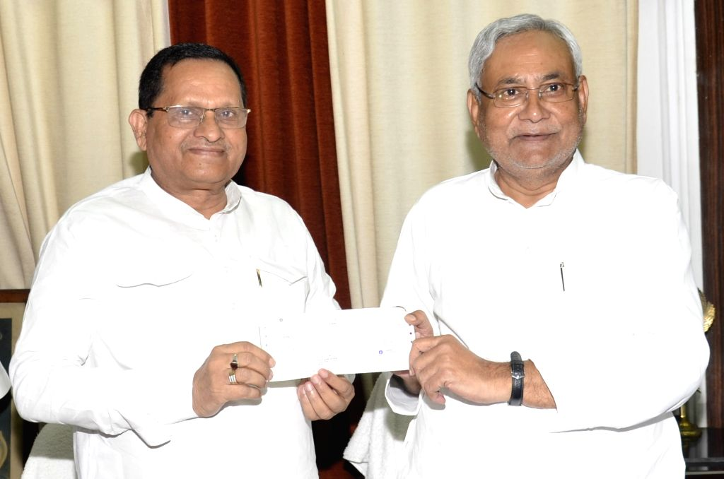 BJP leader Awadhesh Narain Singh presents a cheque to Bihar Chief Minister Nitish Kumar as a contribution to the Chief Minister's Relief Fund in Patna on Sept 11, 2017. - Nitish Kumar and Awadhesh Narain Singh