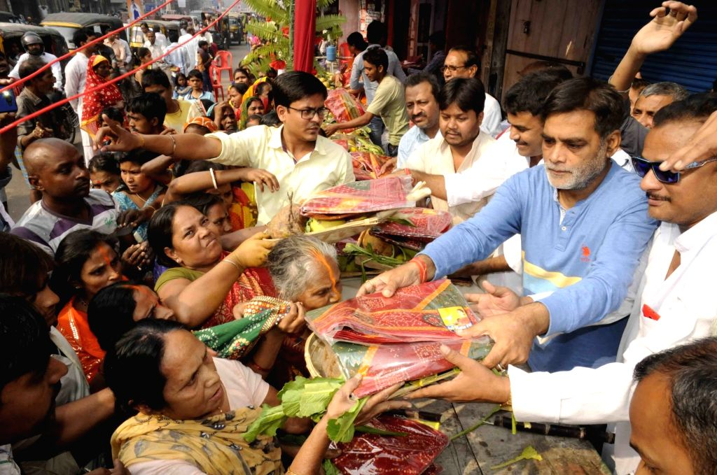 BJP leader Ramkripal Yadav distributes Chhath Puja kit to the devotees in Patna, on Nov 16, 2015.