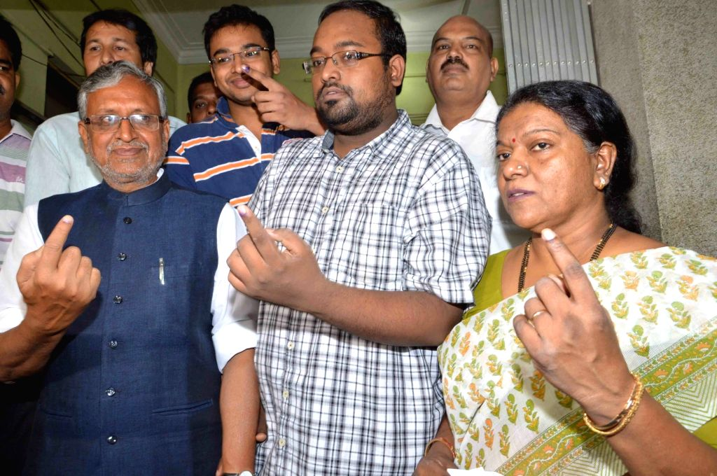 BJP leader Sushil Kumar Modi with his family show their finger marked with phosphorous ink after casting their vote during the third phase of Bihar assembly polls in Patna on Oct 28, 2015.
