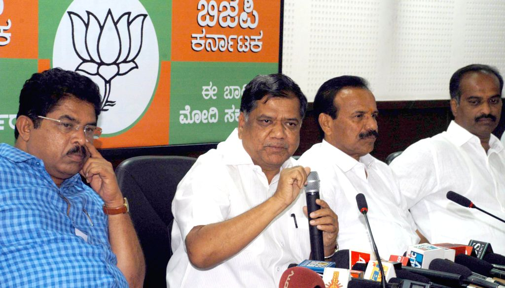 BJP leaders Jagadish Shettar with D V Sadananda Gowda and P. C. Mohan addresses a press conference at BJP office in Bangalore on April 21, 2014.