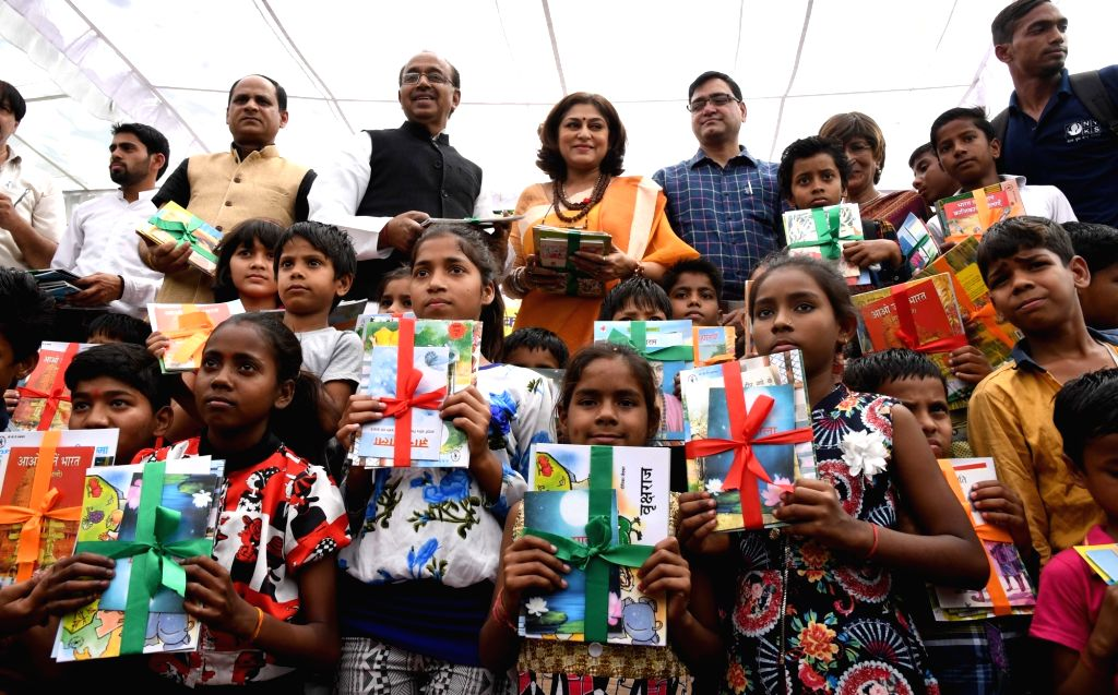 BJP leaders Vijay Goel and Roopa Ganguly distribute books to children during a programme in New Delhi on April 2, 2017.