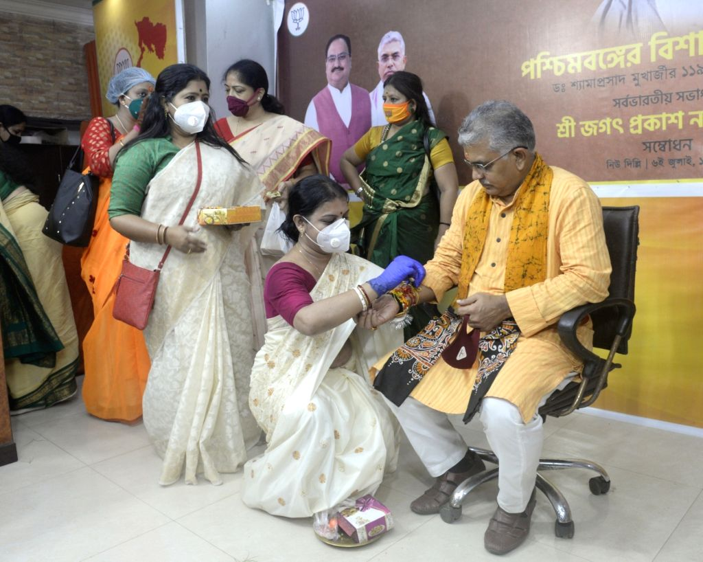 BJP Mahila Morcha activists tie rakhis on the wrist of West Bengal BJP President Dilip Ghosh during Raksha Bandhan celebrations organised at the state party headquarter in Kolkata on Aug 3, ... - Dilip Ghosh