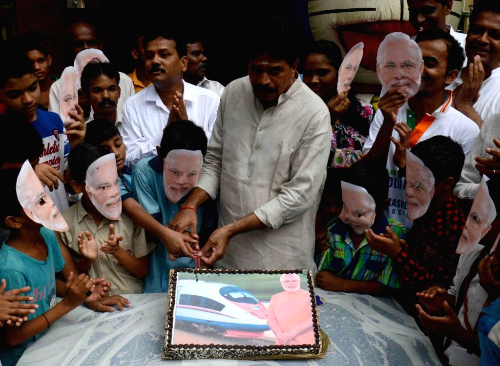 BJP MLA R Tamil Selvan celebrates Prime Minister Narendra Modi's birth day with children by cutting a special cake in Mumbai on Sept 17, 2017. - Narendra Modi
