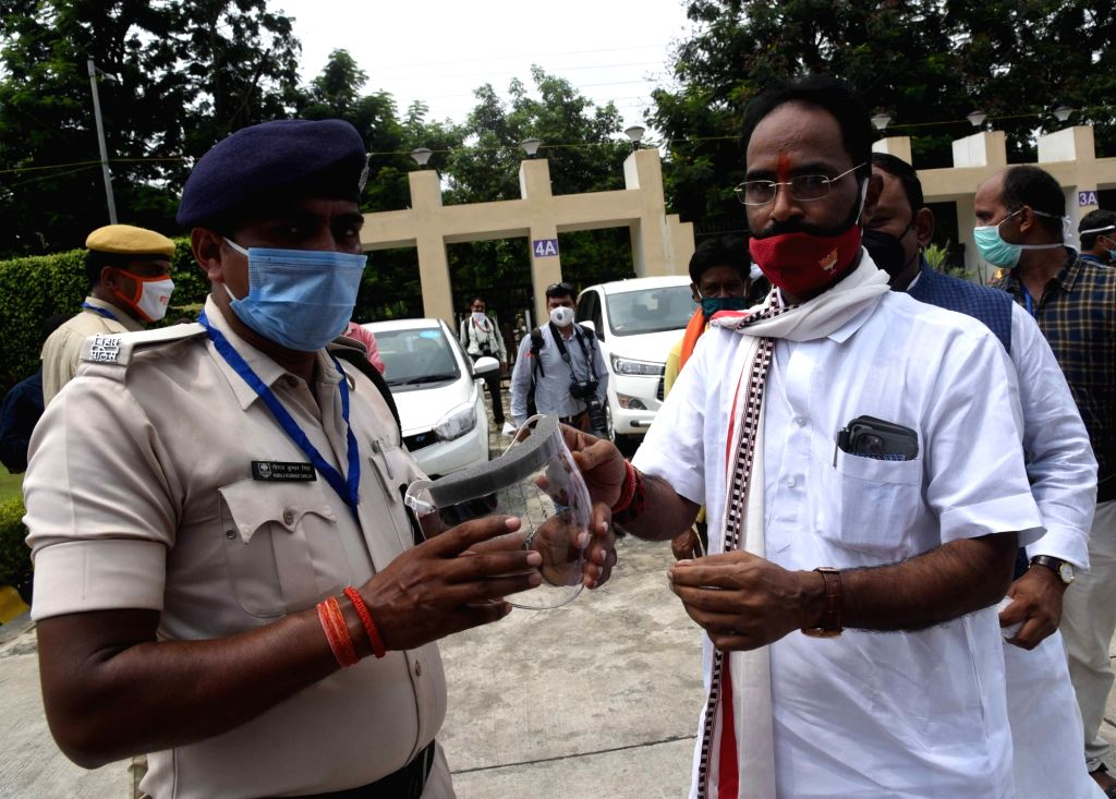 BJP MLC Sanjay Mayukh distributes face shields as he arrives at Gyan Bhawan on the first day of the Monsoon Session of the Bihar Assembly, in Patna on Aug 3, 2020.