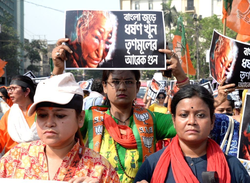 BJP Mohila Morcha activists hold posters during a rally to protest against violence on women in Kolkata on March 30, 2021