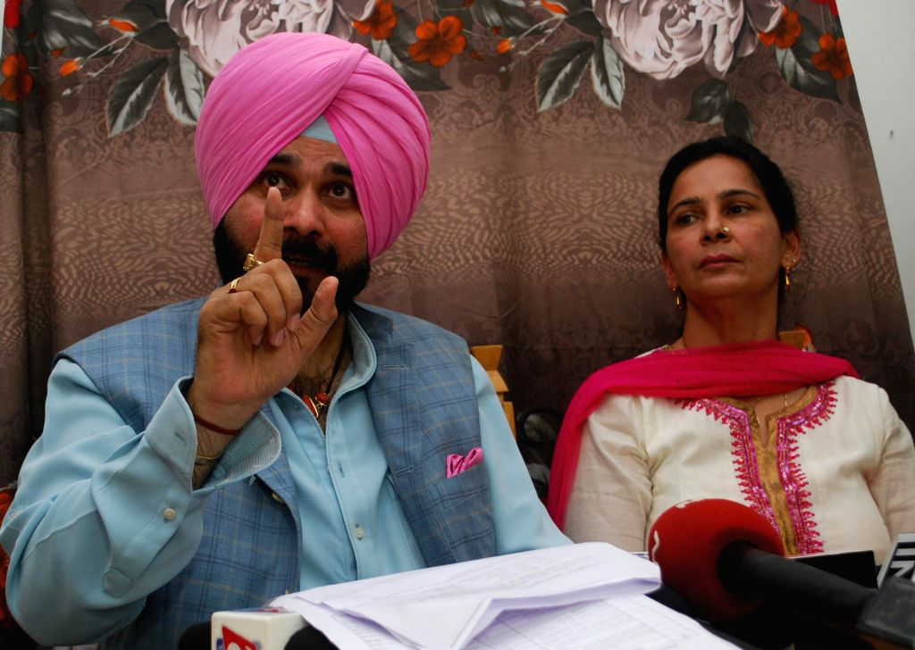 : BJP MP from Amritsar Navjot Singh Sidhu addressing the media at his residence in Amritsar on Sept. 5, 2013. Also seen his wife and BJP MLA from Amritsar Navjot Kaur Sidhu. (Photo: IANS).