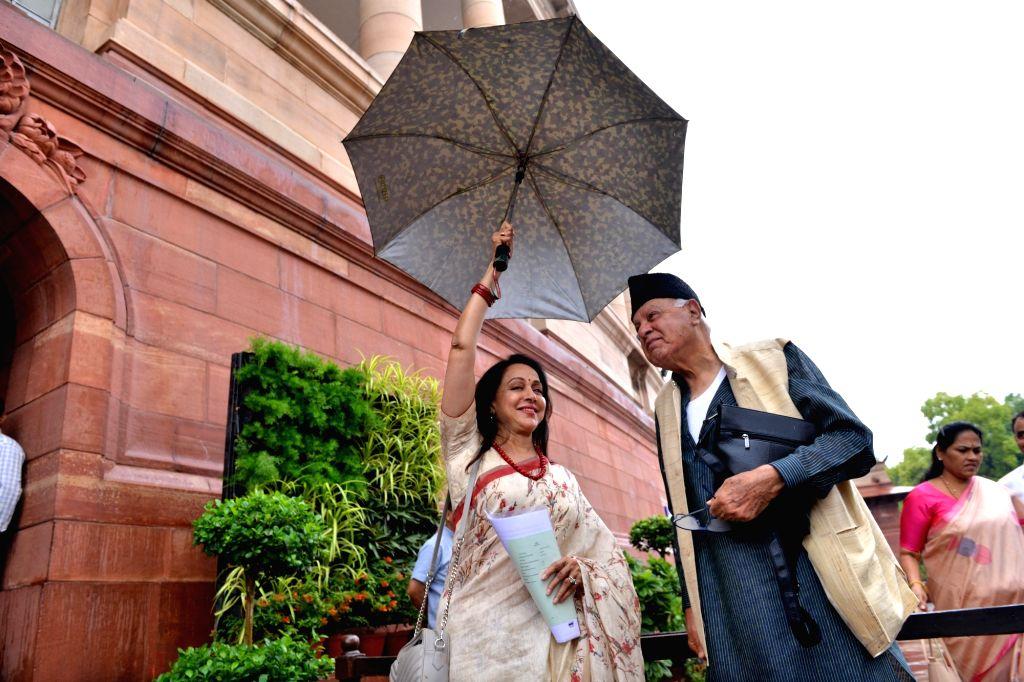 BJP MP Hema Malini shares umbrella with National Conference MP Farooq Abdullah at Parliament in New Delhi on July 18, 2019. - Hema Malini