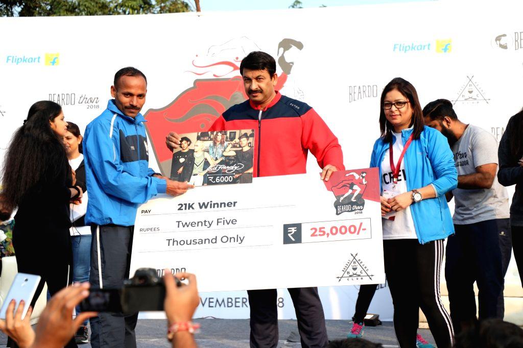 BJP MP Manoj Tiwari felicitates a winner of the run organised to spread awareness regarding men's health, at CWG village sports complex in New Delhi, on Nov 4, 2018.