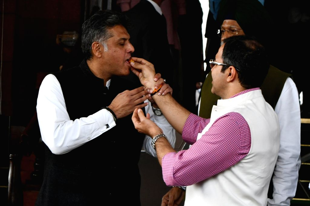 BJP MP Parvesh Verma offers sweet to Congress MP Manish Tiwari after the Parliament passes a bill to grant ownership rights to residents living in unauthorised colonies in Delhi, during ... - Parvesh Verma