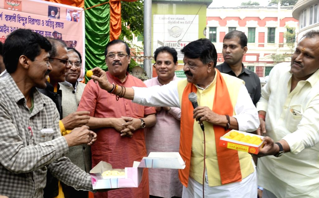 BJP National General Secretary Kailash Vijayvargiya offers sweets to a party leader during celebrations after the Citizenship Amendment Bill (CAB) 2019 was passed in Parliament on Wednesday; ...