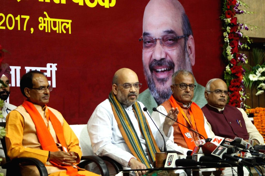 BJP President Amit Shah addresses a press confrence in Bhopal on Aug 19, 2017. Also seen Madhya Pradesh Chief Minister Shivraj Singh Chouhan and Madhya Pradesh BJP chief Nandkumar Singh ... - Shivraj Singh Chouhan, Amit Shah and Nandkumar Singh Chouhan