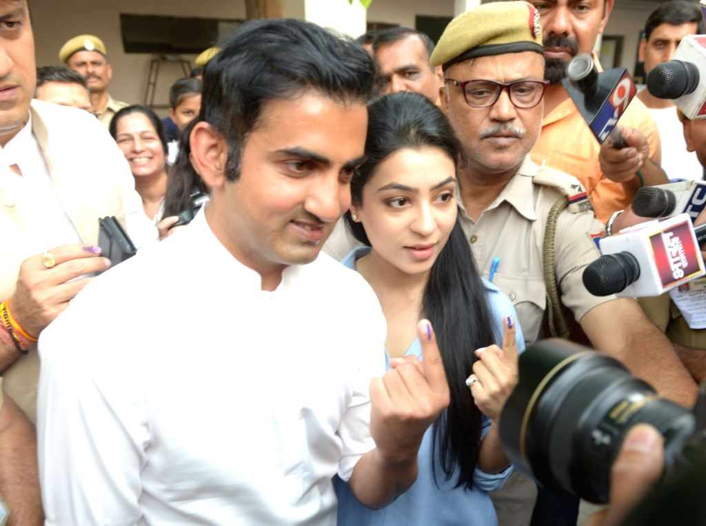 BJP's Lok Sabha candidate for East Delhi, Gautam Gambhir and his wife show their forefingers marked with indelible ink after casting vote during the sixth phase of 2019 Lok Sabha ...