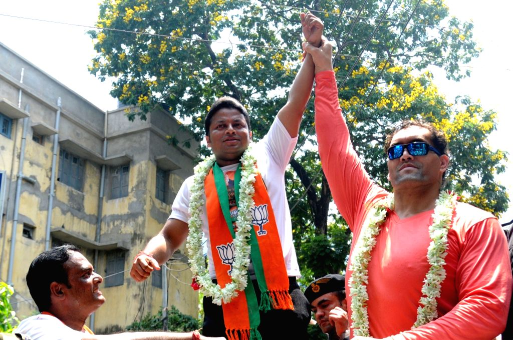 BJP's Lok Sabha candidate from Jadavpur, Anupam Hazra accompanied by WWE wrestler the Great Khali, during an election campaign for the forthcoming Lok Sabha polls, in Kolkata, on April 26, ...
