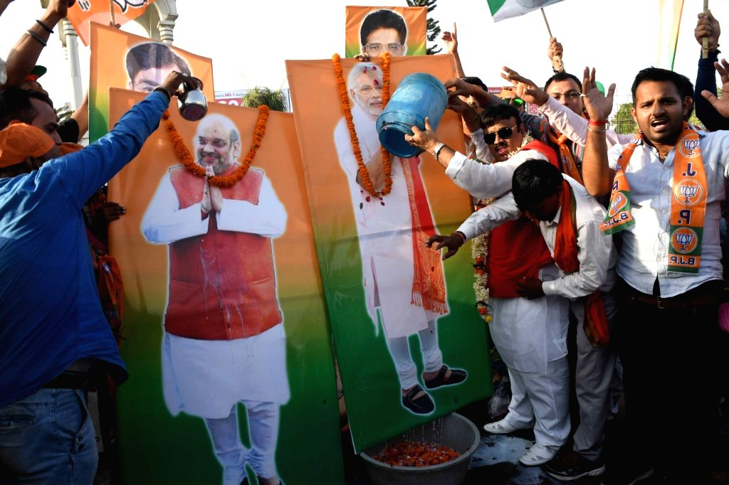 BJP supporters pour milk on the portrait of Prime Minister Narendra Modi and BJP president Amit Shah after BJP-led NDA is set to retain power for another five years after making a sweep of the ... - Narendra Modi and Amit Shah