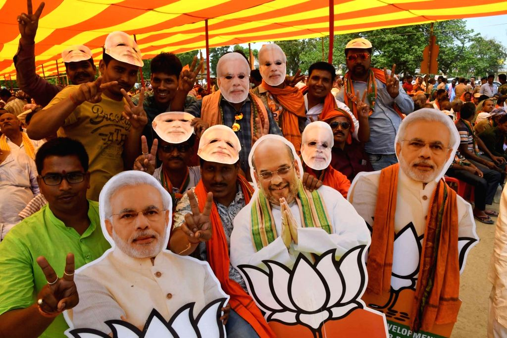 BJP supporters wear face masks and carry cutouts of Prime Minister Narendra Modi and party chief Amit Shah at Shah's public rally in Bihar's Begusarai, on April 24, 2019. - Narendra Modi and Amit Shah