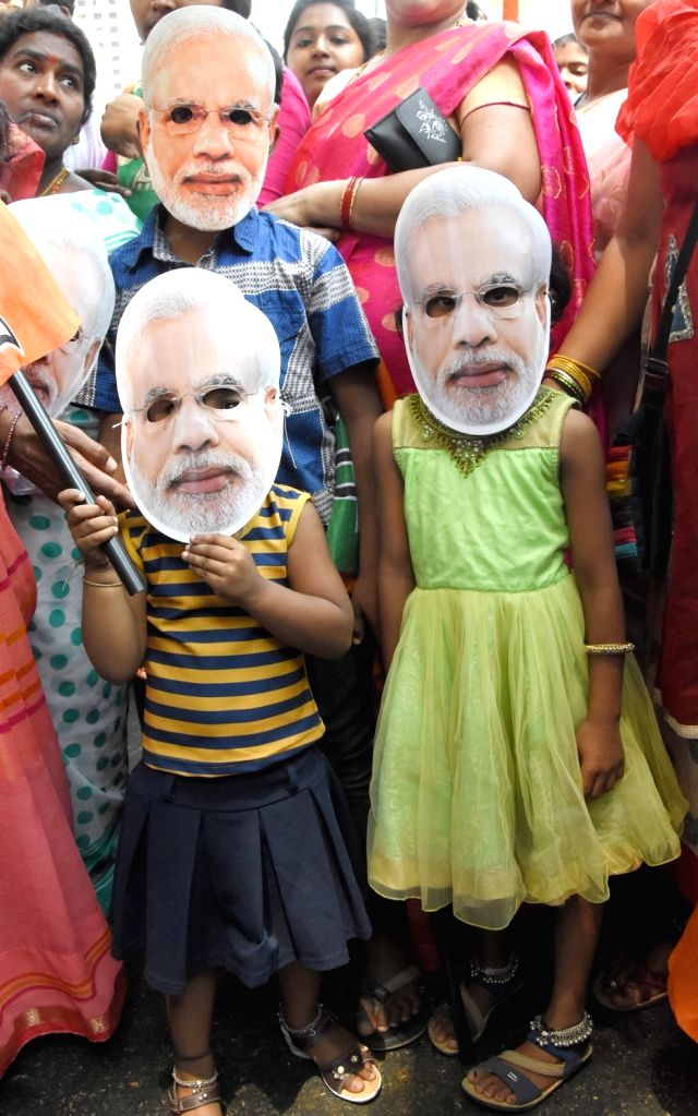 BJP supporters wearing masks of prime Minister Narendra Modi accompanies the party's Lok Sabha candidate from Bengaluru North, D.V. Sadananda Gowda as he heads to file his nomination for ... - Narendra Modi