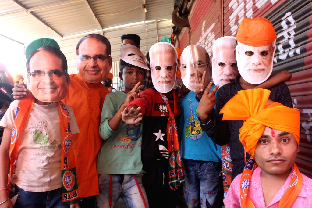 BJP supporters wearing the masks of Prime Minister Narendra Modi, BJP chief Amit Shah and Former Madhya Pradesh Chief Minister Shivraj Singh Chouhan, participate in an election campaign ahead ... - Narendra Modi, Amit Shah and Shivraj Singh Chouhan
