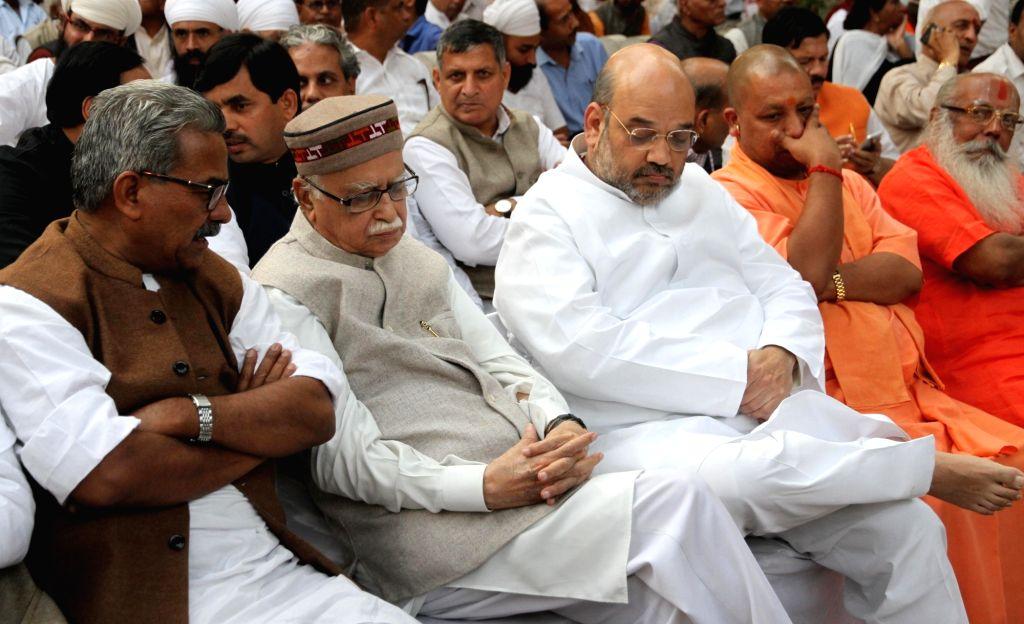 BJP veteran L K Advani, party chief Amit Shah, MP Yogi Adityanath at the cremation of late VHP leader Ashok Singhal in New Delhi on Nov 18, 2015. - L K Advani and Amit Shah