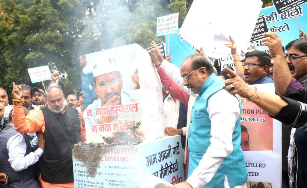 BJP workers led by Union Minister and party leader Vijay Goel burns Aam Aadmi Party's manifesto during a protest in New Delhi, on March 13, 2019.