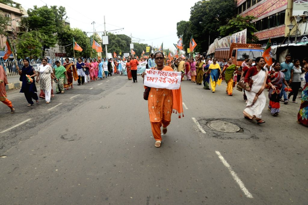 """BJP workers participate in a march to demand publication of a National Register of Citizens (NRC) in West Bengal to drive out """"infiltrators from Bangladesh"""" in Kolkata on Aug 2, ..."""