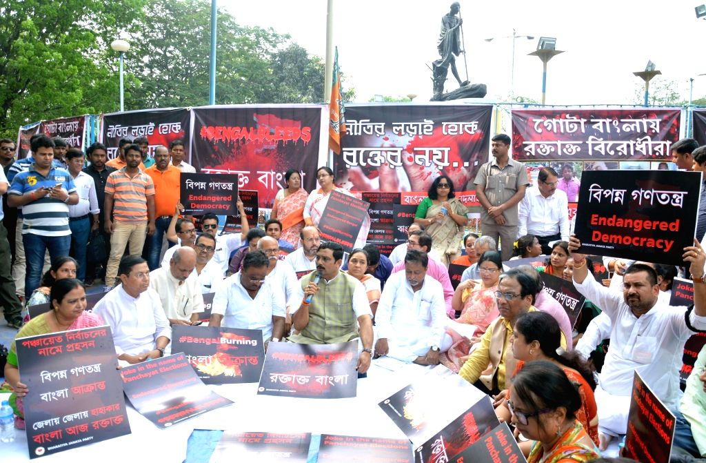 BJP workers stage a demonstration in front of Mayo road Gandhi statue against violence over Panchayat nomination ahead of Panchayat polls in Kolkata on April 6, 2018.