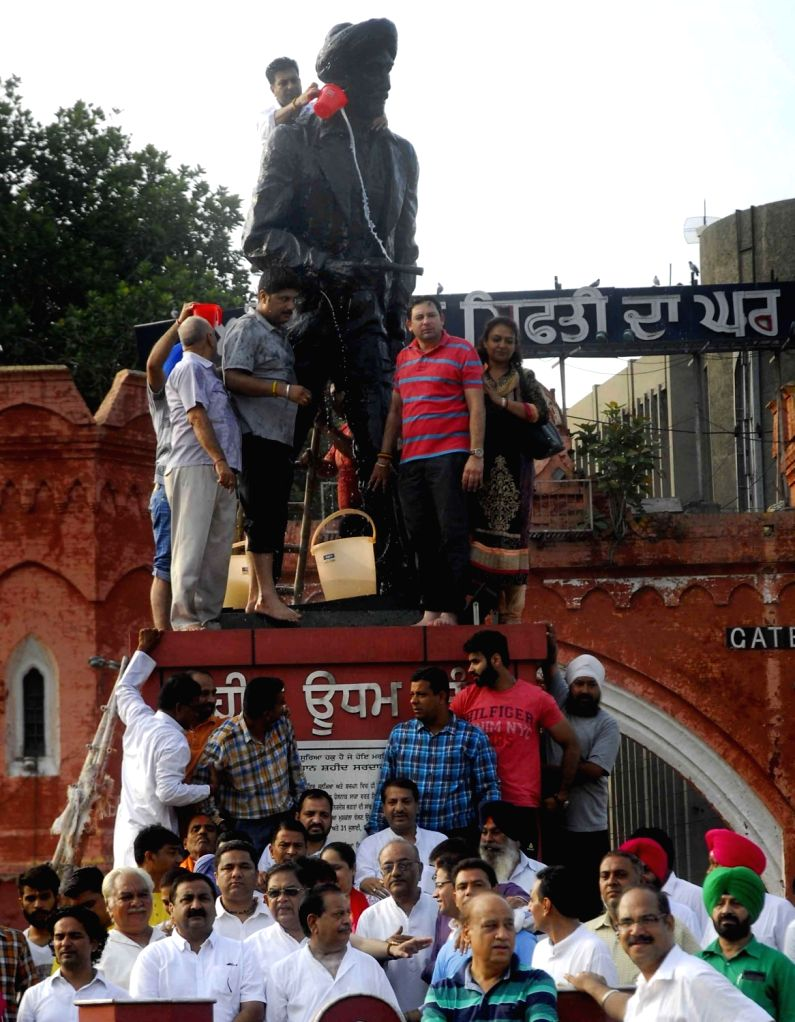 BJP workers wash the statue of  Indian revolutionary Shaheed Udham Singh on his martyrdom day in Amritsar, on July 31, 2016. - Udham Singh