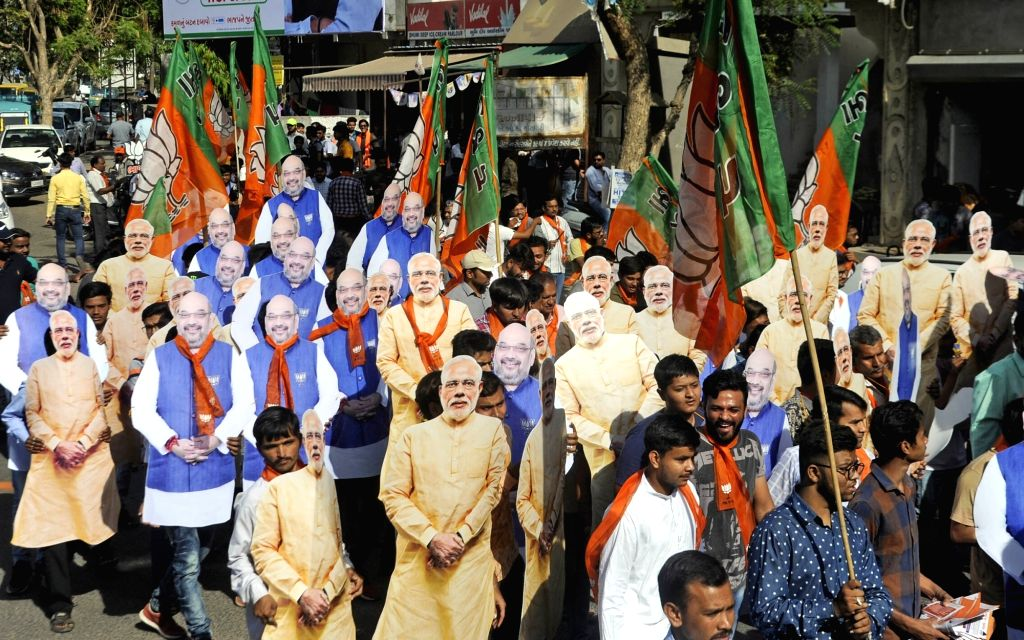 BJP workers wearing the cutouts of Prime Minister Narendra Modi and BJP chief Amit Shah participate in an election campaign for the 2019 Lok Sabha elections, in Ahmedabad, on April 11, ... - Narendra Modi and Amit Shah