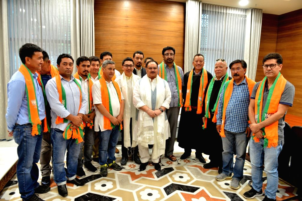 BJP Working President JP Nadda and Ladakh MP Jamyang Namgyal pose for photographs with Ladakhi youth who joined the party, in New Delhi on Aug 26, 2019.