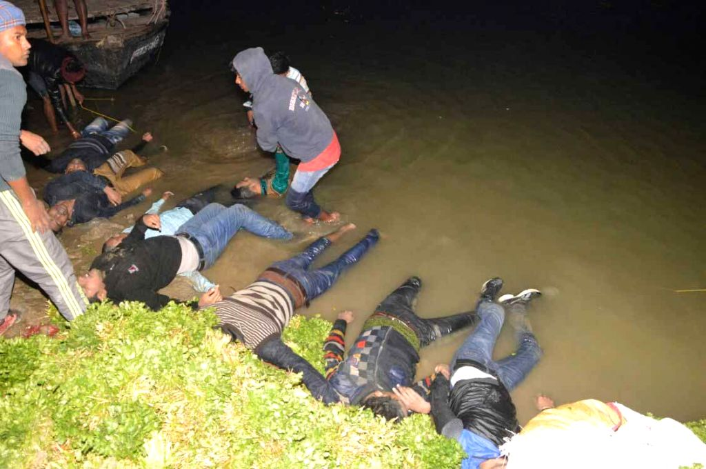 Bodies of the victims of boat accident being fished out of the Ganga river in Patna on Jan 14, 2017. At least 17 passengers were killed and many others were missing as a boat carrying 40 ...