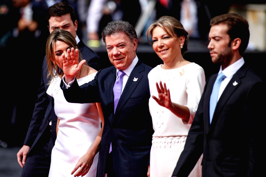 Colombian President Juan Manuel Santos (C) greets people while heading to the National Capitol for his swearing-in ceremony in Bogota, capital of Colombia, on Aug. 7,