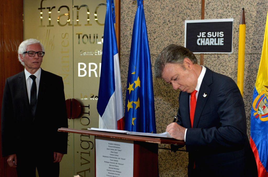 Image provided by Colombia's Presidency shows Colombian President Juan Manuel Santos (R) signing the Book of Condolences for the victims of the attack to the French .