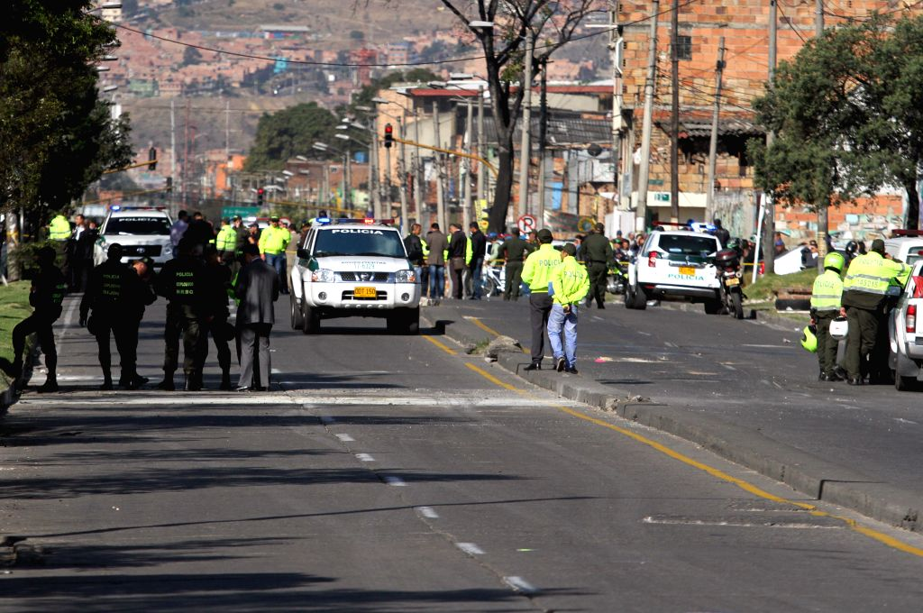 Policemen stand guard at the blast site in Quiroga neighborhood in Bogota, Colombia, on March. 12, 2015. A bomb was exploded as a caravan of 30 policemen circulated ...