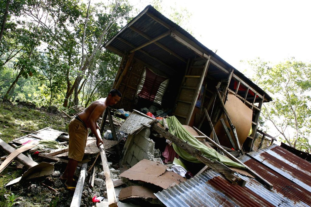 BOHOL, Oct. 16, 2013 (Xinhua/IANS) -- A resident tries to clear his collapsed house after a magnitude 7.2 earthquake in Bohol Province, the Philippines, Oct. 16, 2013. At least 99 people have been confirmed dead in the magnitude 7.2 earthquake in cen