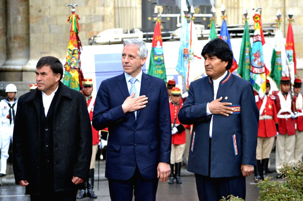 Bolivia's President Evo Morales (R) and Bolivian Vice-President Alvaro Garcia Linera (C) take part in an act to commemorate the Flag Day, in the city of La Paz, ...