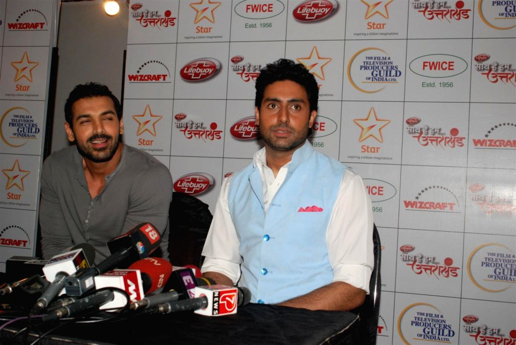 Bollywood actors John Abraham and Abhishek Bachchan during the Star India`s `Saath Hain Hum Uttarakhand` 7-hour programme in Mumbai on August 15, 2013. (Photo::: IANS) - John Abraham and Abhishek Bachchan