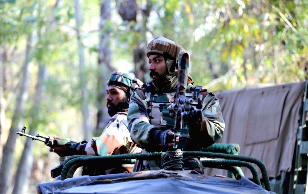 Bongam: Soldiers take position during an encounter with militants in Bongam village of Jammu and Kashmir's Baramulla district on Oct 21, 2015. One separatist guerrilla was killed and three soldiers were injured in the gun fight. (Photo: IANS)