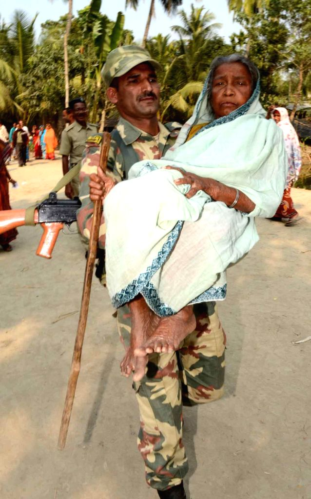 A soldier carries an elderly woman to a polling booth during the by-elections to the Bongaon Lok Sabha constituency in North 24 Parganas district of West Bengal on Feb 13, 2015.