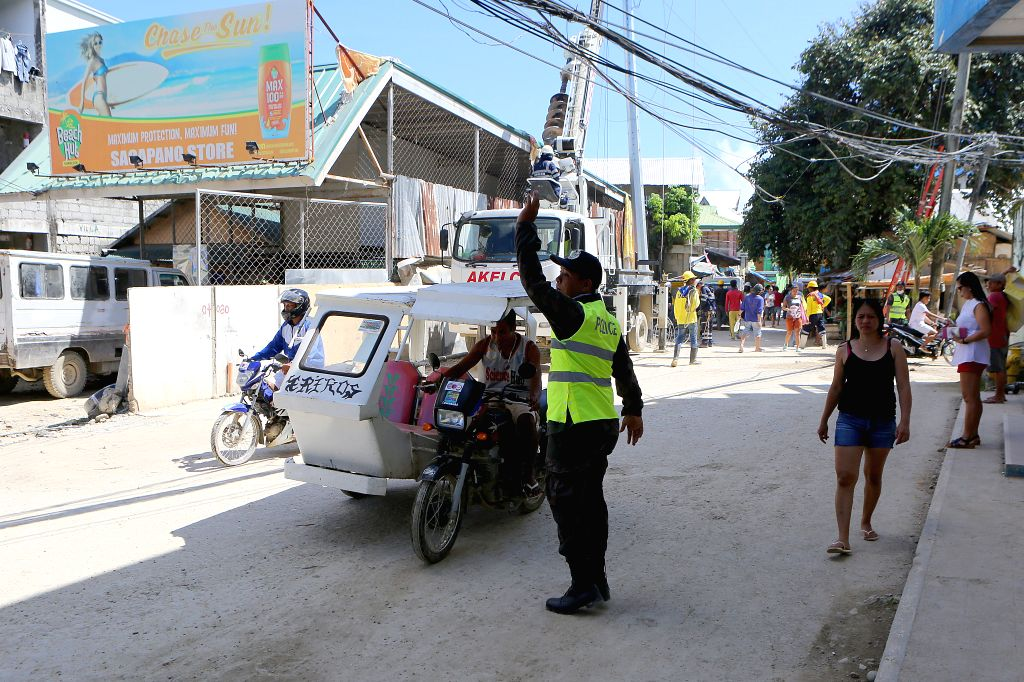 BORACAY ISLAND, Oct. 25, 2018 - A policeman directs traffic on a road on Boracay Island, the Philippines, Oct. 25, 2018. The world famous Boracay resort island in the Philippines will be reopened on ...
