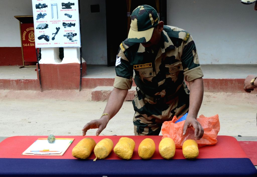 Border Security Force (BSF) Deputy Inspector General Bhupender Singh and BSF officials show six packets of heroin recovered from a Pakistani smuggler at BOP Rajatal near Amritsar on Sunday ...