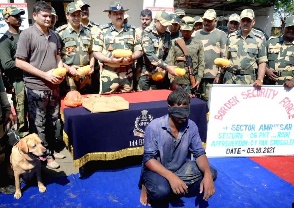 Border Security Force (BSF) Deputy Inspector General Bhupender Singh and BSF officials show six packets of heroin recovered from a Pakistani smuggler (C) at BOP Rajatal near Amritsar on ...