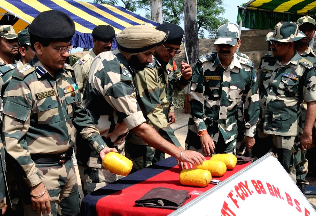 Border Security Force (BSF) officers present before press around four kg heroin and other items recovered from a drug smuggler near the Border Out Post (BOP) Ramkot, some 36 km from ...