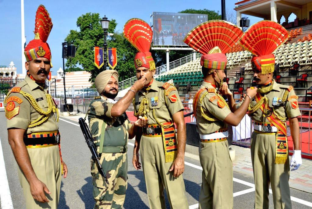 Border Security Force (BSF) soldiers exchange sweets during the 74th Independence Day celebrations at the Attari-Wagah Border in Attari of Punjab's Amritsar district on Aug 15, 2020.