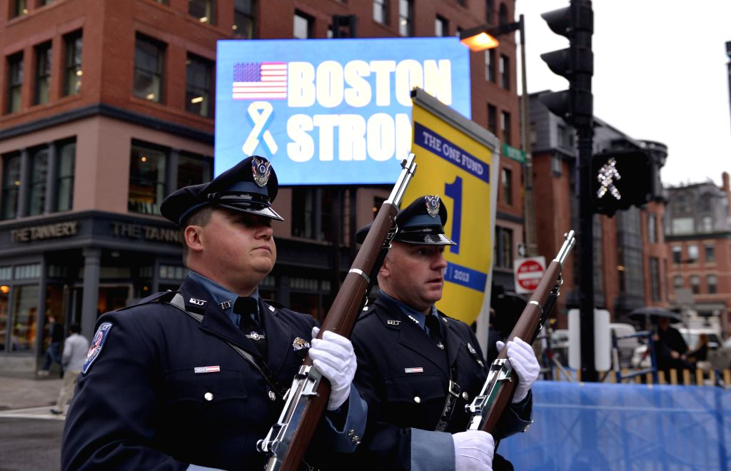 Policemen pass by a screen near the site where explosions occured during the 2013 Boston marathon, in Boston, Massachusetts, the United States, April 15, 2014. Twin